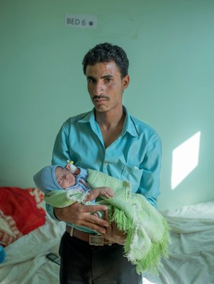 "A father holds his baby at the Mother and Child Hospital after the child was treated for a respiratory infection. Doctors and nurses have fled Yemen, leaving hospitals stretched thin. ""A lot of my colleagues have already left or are trying to travel to the Gulf states to find a better life,"" says one Yemeni doctor working in Sanaa. Taiz, Yemen 2018. © Matteo Bastianelli"