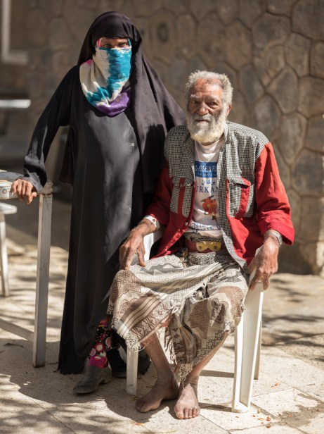 Abadi Muthanna, 70, sits outside the Al-Nasser Hospital in Ad Dali with his pregnant 35-year-old wife, Iman. He suffers from high blood pressure and heart problems. Yemen's depleted health system relies on humanitarian organization to provide medical care. Ad Dhale, Yemen 2018. © Matteo Bastianelli