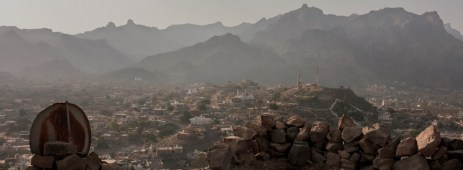 A view of the city beyond a barricade of stones on top of a building in ruins, used by President Hadi's coalition to fight off the Houti rebels. Ad Dhale, Yemen 2018. © Matteo Bastianelli