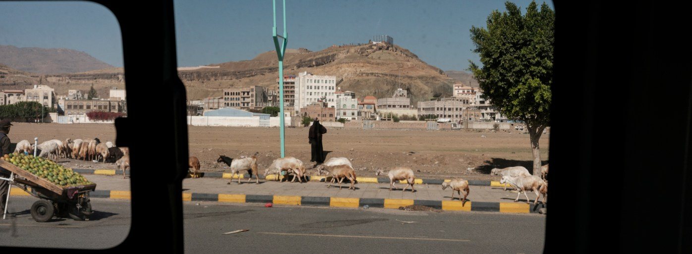 A woman leads her sheep to graze while a man is seen carrying his charge of prickly pears along the street. Sana'a, Yemen 2018. © Matteo Bastianelli