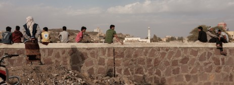 Some men sitting on a wall during a football match. Life goes on despite the war that has been ravaging the country for 4 years. Ad Dhale, Yemen 2018. © Matteo Bastianelli