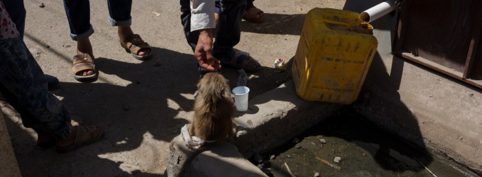 Some men are seen feeding a little monkey in the street while someone fills a jug with water from a fountain. According to the United Nations, the Yemen crisis has become the world's worst humanitarian crisis, around 20 million people are in need of protection and humanitarian assistance due to the lack of health services and supplies caused by the ongoing war and blockade. Ad Dhale, Yemen 2018. © Matteo Bastianelli