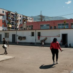 40-year-old Orkida Driza walks towards her home, while two boys are seen carrying their drums slung over their shoulders. Most of the men living in the settlement make a living working as waste pickers or playing drums in the street. Tirana, Albania 2019. © Matteo Bastianelli