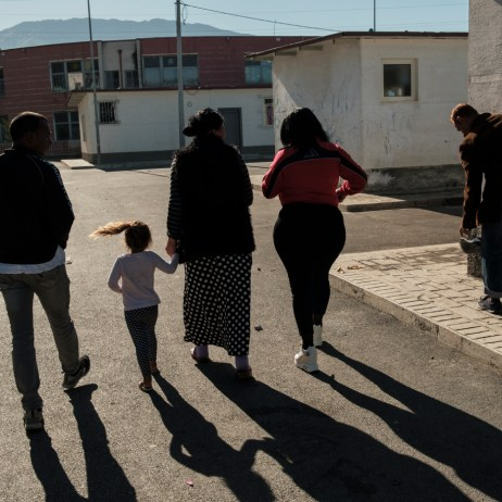 """40-year-old Orkida Driza is seen walking along with other members of the Romani community living in the settlement. Orkida was given in marriage at the tender age of 14 by her family, she's divorced now and has five children. She is currently the leader of the Roman Organization """"Catia e Gruas Rome"""", which stands for the rights of the Roma minorities in Tirana, Albania 2019. © Matteo Bastianelli"""
