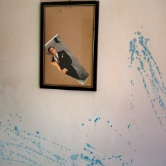Half of a torn wedding photo of the groom, hanging on a wall inside a Roma community settlement in Tirana. Child marriage affects girls in far greater numbers than boys. According to Save the Children, every year, 12 million girls and young women all over the world marry before the age of 18. Tirana, Albania 2019. © Matteo Bastianelli
