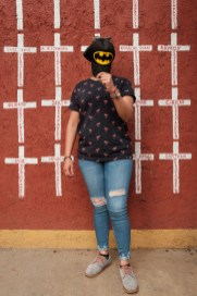 "27-year-old Jeimy Elisuath Hernández, who came from Peñablanca Cortés, Honduras, is seen portrayed while hiding her face with her Batman's hat. Behind her, a wall painted with crosses reporting the names of migrants who found shelter in ""Casa del Buen Samaritano"" and, after starting their journey to the US border, they disappeared. Jeimy left Honduras on February 2019 due to the presence of gangs near her home and covered her face for fear of repercussions. She hopes to get to the USA in order to have a peaceful life. Oaxaca de Juarez, Mexico 2019. © Matteo Bastianelli"