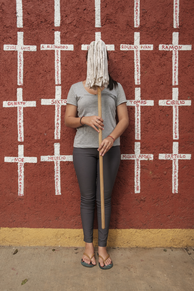 "16-year-old Jessica, who came from Peñablanca Cortés, Honduras, is seen portrayed while hiding her face with a mop. Behind her, a wall painted with crosses reporting the names of migrants who found shelter in ""Casa del Buen Samaritano"" and, after starting their journey to the US border, they disappeared. Jessica left Honduras because of the violence in her region and covered her face for fear of repercussions. She hopes to get to USA. Oaxaca de Juarez, Mexico 2019. © Matteo Bastianelli"