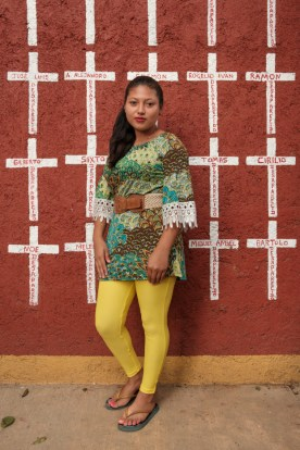 "19-year-old Cindy Janeth Flores Rodriguez, who came from San Pedro, Honduras, is seen portrayed at the shelter of ""Casa del Buen Samaritano"". Behind her, a wall painted with crosses reporting the names of migrants who found shelter there and, after starting their journey to the US border, they disappeared. Cindy left Honduras on August 2019 and has now applied for asylum in Mexico. Oaxaca de Juarez, Mexico 2019. © Matteo Bastianelli"