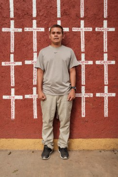 "34-year-old Edwin Noel Mejía Nolasco, who came from Honduras, is seen portrayed at the shelter of ""Casa del Buen Samaritano"". Behind him, a wall painted with crosses reporting the names of migrants who found shelter there and, after starting their journey to the US border, they disappeared. Nevertheless, Edwin hopes to reach his relatives in South Carolina. Oaxaca de Juarez, Mexico 2019. © Matteo Bastianelli"
