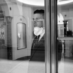 """A salesperson at a luxury shop in via dei Condotti, is seen portrayed with a mask around the neck while looking outside the window. Streets and shops of the city centre are almost deserted, after the Prime Ministerial Decree """"I stay home"""", which disposed that people shouldstay home except forwork needs, situations of necessity and health reasons. Rome, Italy 2020. © Matteo Bastianelli"""