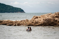 A couple is seen bathing on the Hornos beach in Acapulco. One of the oldest beach resorts in Mexico, once known as a holiday destination for Hollywood stars and millionaires, Acapulco has recently been ranked as the second most violent city in the world in 2018 with a rising number of extortions, kidnappings, and murders. Its beaches are now almost deserted, except for a few locals, and constantly patrolled by policemen. Acapulco, Mexico 2019. © Matteo Bastianelli