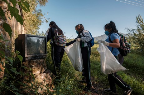 Three student volunteers of a local school, armed with masks, gloves and trash bags to clean the area, are seen walking by an old television dumped near the river. Santiago Huajolotitlán, Mexico 2019. © Matteo Bastianelli