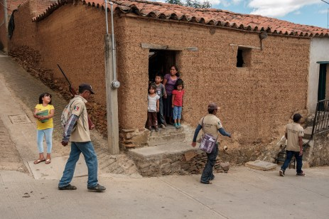 "Some members of the ""Policia Ciudadana y Popular"" are seen patrolling the road while a family, standing at the doorstep of their home, looks on with concern. The local indigenous community feels abandoned and not protected by the State of Guerrero, the second-poorest and most violent state in the country. The PCP's members try to prevent violence and criminal activities, but the fact that they go around armed, also worry the community. Temalacatzingo, Mexico 2019. © Matteo Bastianelli"