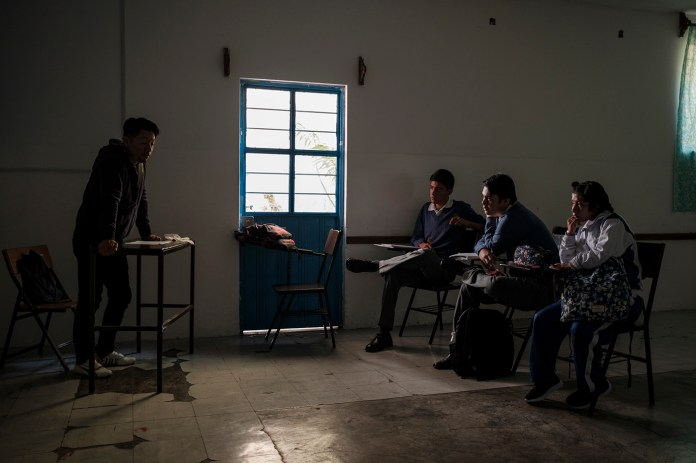 "Three students are seen listening to their teacher at the ""Unidad Escolar Josè Clemente Orozco"". Tehuacán, Mexico 2019. © Matteo Bastianelli"