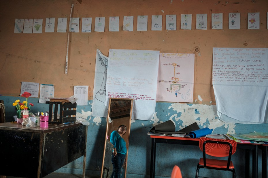 """34-year-old Citlali Pérez Vázquez, teacher and leader of the """"Policia Ciudadana y Popular"""", is seen inside the classroom where she works. On the wall there are the Spanish and Nahuatl alphabets, both spoken by the indigenous community in Santa Cruz Loma Lapa, Mexico 2019. © Matteo Bastianelli"""
