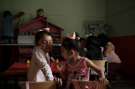 """Two little girls are seen talking to each other seated at their desk in the classroom of a center for child development, run by the NGO """"Semillita de Esperanza"""" (Little Seeds of Hope), where children can play and do art and craft activities, giving them the possibility to develop their imagination and creativity. Alcozauca de Guerrero, Mexico 2019. © Matteo Bastianelli"""