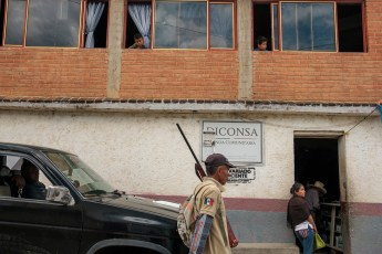 "A member of the ""Policia Ciudadana y Popular"" patrols the road while some people and kids look on. The local indigenous community feels abandoned and not protected by the State of Guerrero, the second-poorest and most violent state in the country. The PCP's members try to prevent violence and criminal activities, but the fact that they go around armed, creates concern among the community. Temalacatzingo, Mexico 2019. © Matteo Bastianelli"