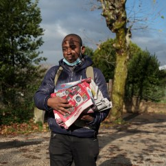 Anthony Ehikwe, a 28-year-old Nigerian refugee, portrayed while holding hundreds of fliers in the hands during a working day on the outskirts of Rome. As being of Christian faith, he was forced to flee his native country to escape religious persecution by Islamist terrorist groups. He has been living in Italy for 4 years now and he received the status of refugee with humanitarian protection. He currently lives in a reception centre in the municipality of Rocca di Papa and works off the books as flyer distributor. Rome, Italy, December 2020. © Matteo Bastianelli/National Geographic Society Covid-19 Emergency Fund