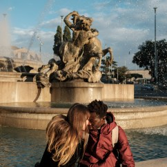 """21-year-old Lamine Sane and his 19-year-old girlfriendGiorgia Giannetti, are seen in a tender moment in front of the Naiadi Fountain in Piazza della Repubblica. Lamine was born in Gambia, but he was raised by a family in Senegal. At the age of 15 he decided to meet his biological family and went to visit them, but after 3 days, a group of rebels slaughtered his father in front of him tosteal his cows. """"Escape Lamine, run away"""". His father told him before to be killed. From Gambia to Mali, then Burkina Faso, Niger and through the desert, he arrived in Libya. When he was rescued at sea in Italy, he was among the few people who survived theshipwreck. In 2016 he met Giorgia, who was volunteering to teach Italian language to refugees at the Reception Centre for Asylum Seekers (CARA) in Castelnuovo di Porto and when the center was closed in 2018, Lamine was hostedat Giorgia's parents house for a while. Lamine, issued with a residence permit for subsidiary protection expiring in 2024, is working for a furniture company in Rome, while Giorgia is currently finishing her studies in Human Sciences to become a cultural mediator. They hope to rent an apartment soon to start living together. Rome, Italy, November 2020. © Matteo Bastianelli/National Geographic Society Covid-19 Emergency Fund"""