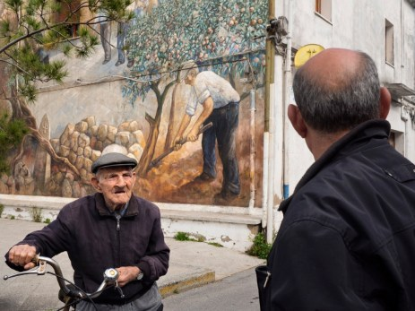 101-year-old Giulio Podda, talks with his son Fulvio in a street in their village. Everyday Giulio goes out for a ride on his bike, cycling for at least 3 km. San Sperate, Italy 2015. © Matteo Bastianelli