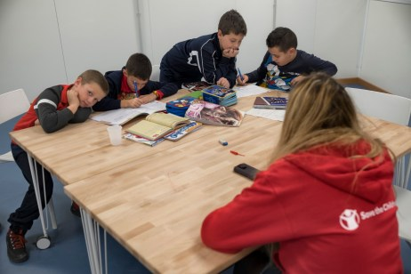 Some kids are seen doing their homework followed by a teacher from Save the Children, at the 2.0 Youth Center. Amatrice, Italy 2016. © Matteo Bastianelli