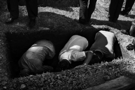 Family members of a victim lay the coffin of their beloved one in a grave. On the anniversary of the massacre of Prijedor, 284 victims found after 22 years in a mass grave in Tomasica were returned to their relatives. Zecovi, Republic of Srpska, Bosnia and Herzegovina, 2014. © Matteo Bastianelli