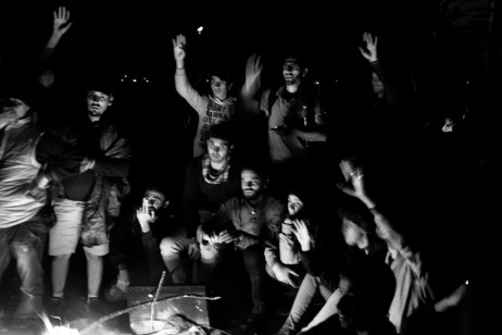 A group of Syrian refugees thrust their hands up after one of them asked the others who wanted to go to Germany. They were kept at the border between Greece and FYROM for 5 days. Idomeni, Greece 2015. © Matteo Bastianelli