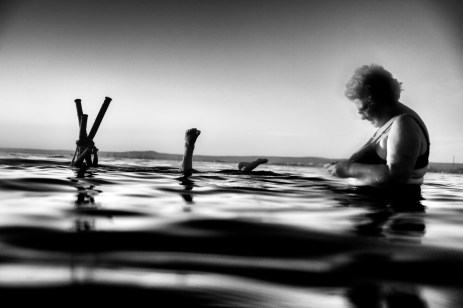Anna and Franco on holiday in San Vito, in the Big Sea. While Franco dives to collect the mussels from a wooden stake, Anna gets ready to taste them. Taranto, Italy 2013. © Matteo Bastianelli