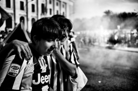 Giulia and her son Tommaso D'Ippolito celebrate the victory of the national league of their favourite football club. Son of an ex-worker at the historic local steelworks, Tommaso has been affected with a rare form of Goldenhar syndrome from birth, caused by genes transmitted by his father Achille, exposed for more than thirty years to contamination at the Ilva steelworks. Taranto, Italy 2013. © Matteo Bastianelli