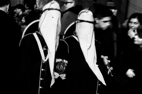 """Two members of the Confraternity of Mysteries during the procession in Holy Week. The """"perduni"""", members of the Confraternity with their hoods pulled low over their eyes, walk slowly, swaying on their legs for about 13 hours until their return to the church. Taranto, Italy 2013. © Matteo Bastianelli"""