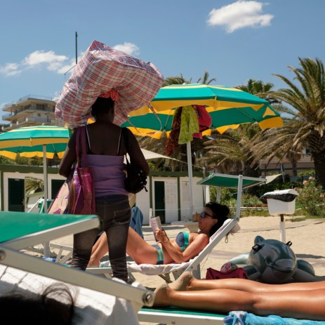 A peddler walks on the beach while some victims of the earthquake of 24 August 2016 are seen resting on the beach loungers in front of the hotel where they are temporarily staying. Grottammare, Italy 2017. © Matteo Bastianelli