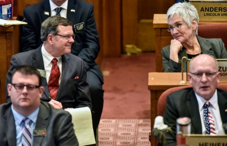 Sen. Mike Vehle, left, and Rep. Tona Rozum, right, share a laugh as Gov. Dennis Daugaard delivers his state of the state address in the House Chambers of the state capitol on Tuesday in Pierre. (Matt Gade/Republic)