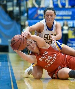 South Dakota State Jackrabbits guard/forward Kerri Young (10) scrambles for a loose ball with South Dakota Coyotes center Kate Liveringhouse (34) along the sideline during a game on Sunday at Frost Arena in Brookings. (Matt Gade/Republic)
