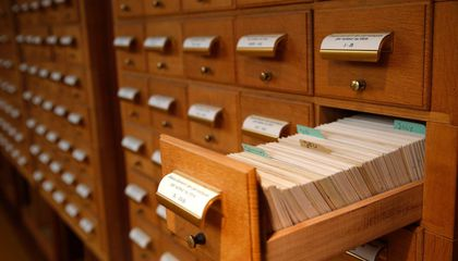 A row of drawers in a library. One drawer is opened and is filled with old library catalog cards.