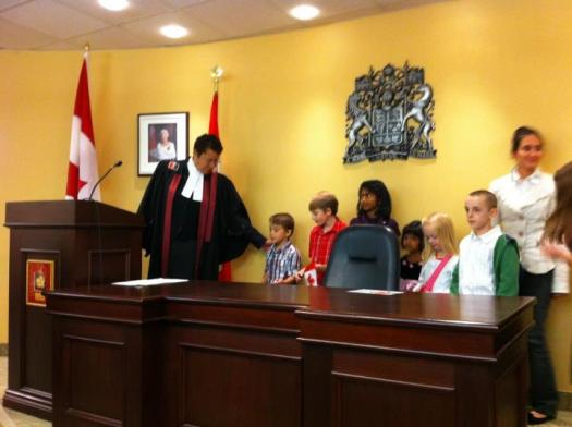 Citizenship Judge, Linda Carvery invites children to join her to sing O'Canada.
