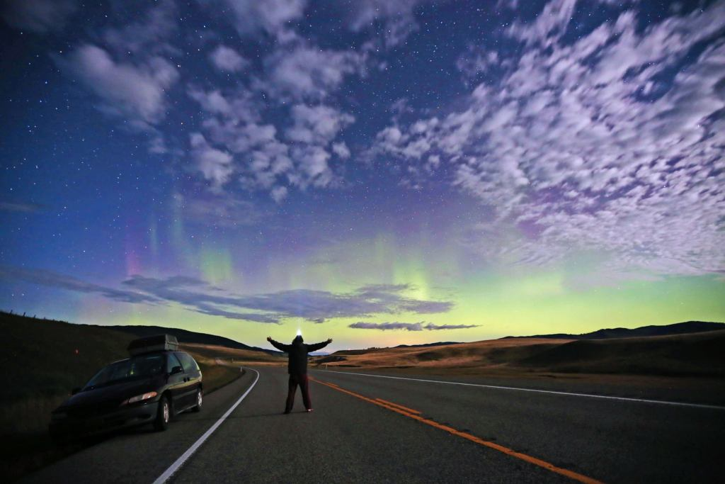 the northern light illumintate the sky as a man looks up