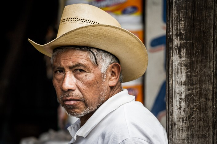 a guatemalan man with a coyboy hat looks directly at the camera