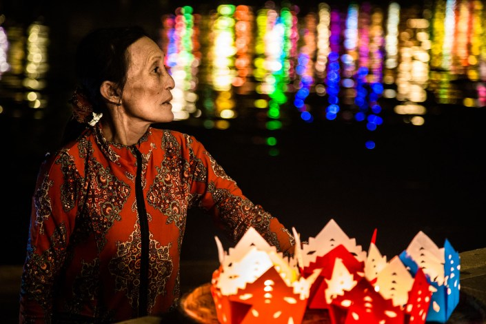 portrait of a woman selling candles to float down the river in hoi an veitnam