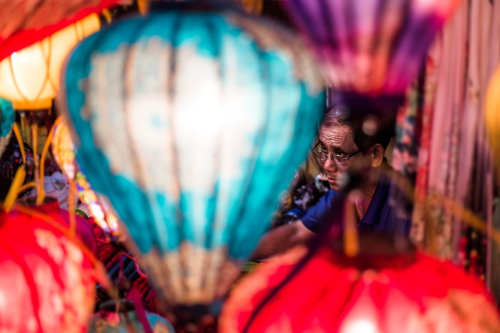 a man surrounded in lanterns works on making another one in hoi ann