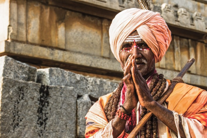 a local indian holy man offers a blessing in hampi
