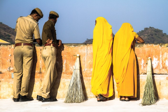 two guards talk to two women outside in the redfort in india