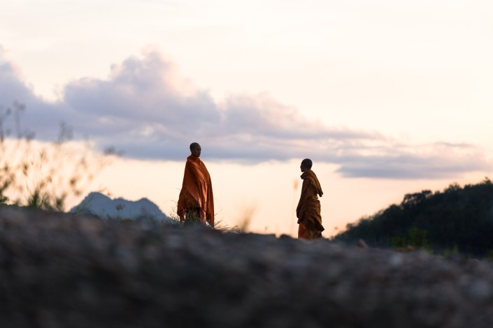two monks stand in the distance as the sun sets