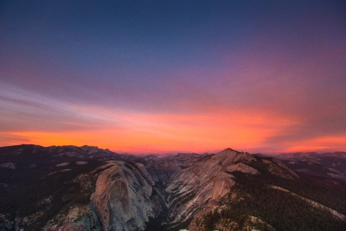the sun sets casting soft light over the yosemite valley