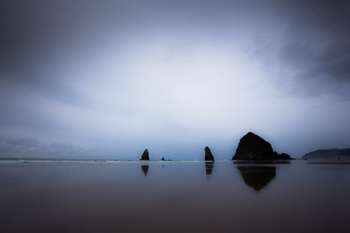 fog covers the iconic rock monoliths at canon beach