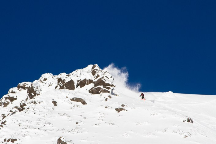 Skier making big turns down a steep face in the Annapuri backcountry japan