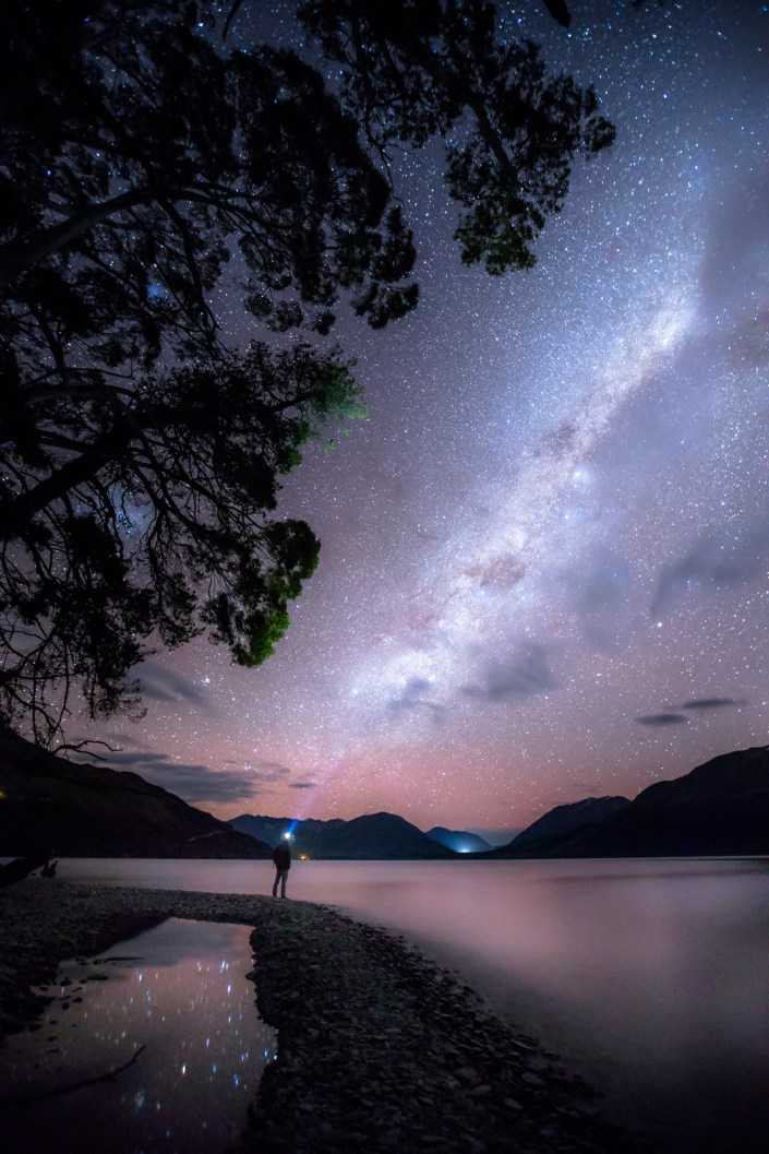 a person stands under the milky way on the shoreline of the Queenstown Lake