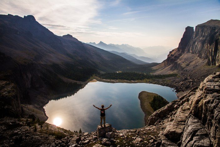 a man stands on a rock above a lake far down below in the alpine