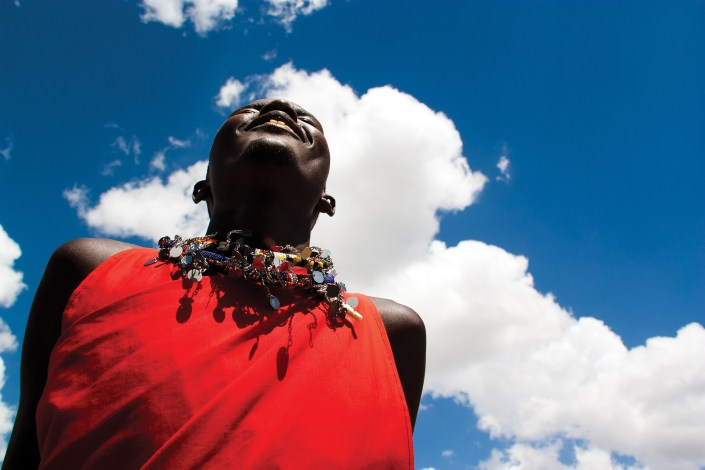 A Maasai Warrior jumps high into the air with blue skies in the background