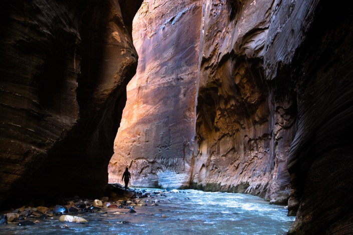 A person hikes along steep canyon walls of zion national parks narrows