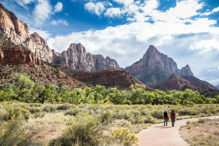 A couple of hikers walk a trail in Zion National Park